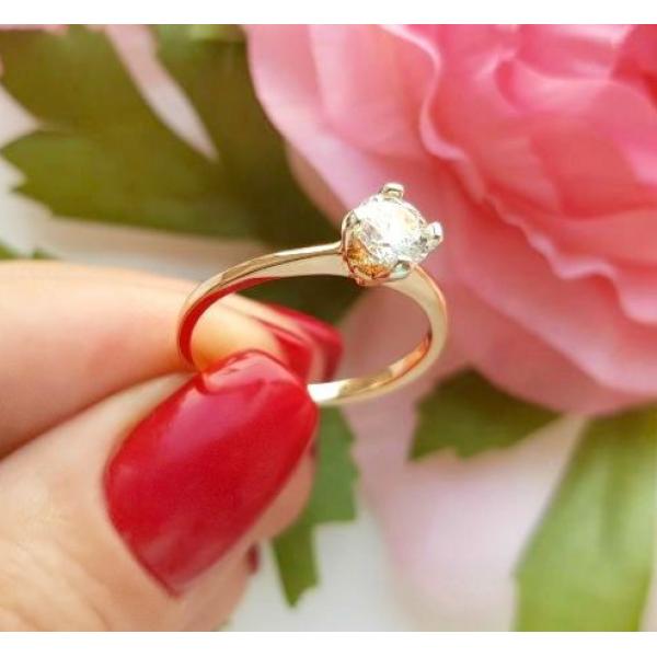 Кольцо позолоченное с фианитом RIF-0185 на фоне цветов